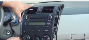 Use a panel removal tool to unclip side panels from radio