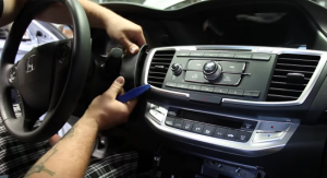 Use a plastic removal tool to release the panel to the left of the radio