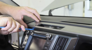 Using an automotive trim tool to remove the upper dashboard trim panel. Set the panel aside once removed