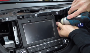 Use a screwdriver to remove four screws that hold the original car radio on the dashboard