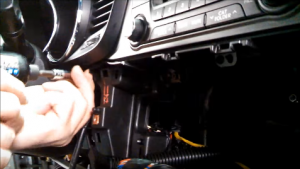 Unscrew screws to release the panel on the left side of the radio and the radio trim panel