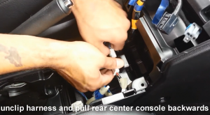 Unclip harness and pull rear center console backwards