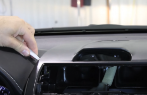 Gently pry the upper dashboard housing from the radio's trim bazel using either an automotive trim tool or your hands