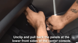 Unclip and pull back the panels at the lower front sides of the center console