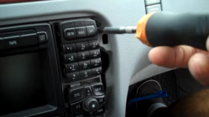 Remove four T20 Torx screws that are holding the radio on the dashboard