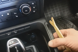 Use the removal tool to pop out the panel beside the gear shift
